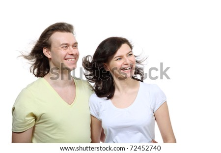 Portrait of a young couple in love looking to a side, he embraces girlfriend