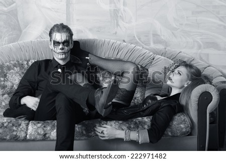 Portrait of a young couple in the Halloween mask. Man and woman on sofa - stock photo
