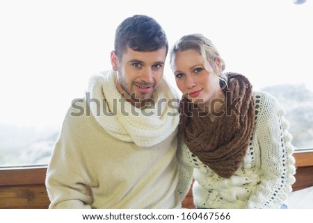 Portrait of a young couple in winter clothing sitting against window