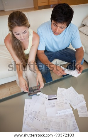 Portrait of a young couple looking at their bills in their living room - stock photo