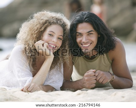 Portrait of a young couple lying on the beach and smiling - stock photo