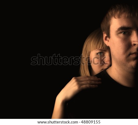 portrait of a young couple on a black background - stock photo