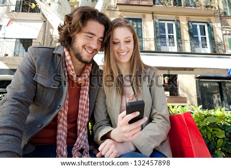 Portrait of a young couple on vacation in a destination city, sitting down with shopping bags and using a smartphone device during a sunny day.