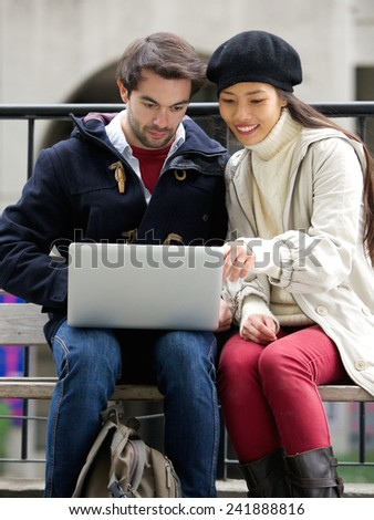 Portrait of a young couple sitting outdoors looking at laptop together