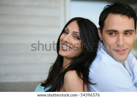 Portrait of a young couple smiling back to back