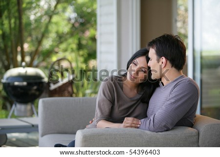 Portrait of a young couple smiling on a sofa - stock photo