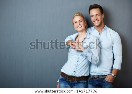 Portrait of a young couple standing against blue gray background - stock photo