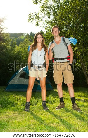 Portrait of a young couple standing in front of a tent - stock photo