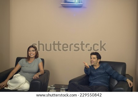 Portrait of a young couple watching a movie with a projector