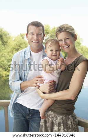 Portrait of a young couple with baby girl standing against the lake - stock photo