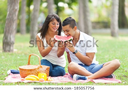 Portrait of a young couple with  eating watermelon at a picnic - stock photo