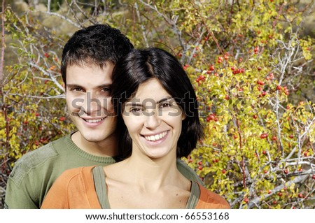 portrait of a young couple with flowers behind them - stock photo