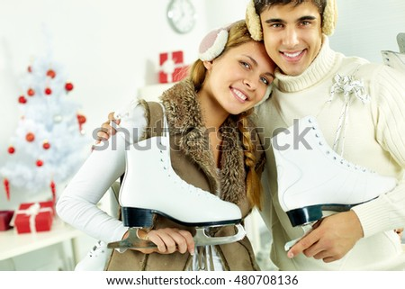 Portrait of a young couple with skaters embracing, looking at camera and smiling