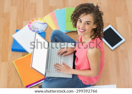 Portrait of a young creative businesswoman working on laptop - stock photo