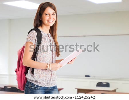 Portrait of a young cute student in her classroom - stock photo