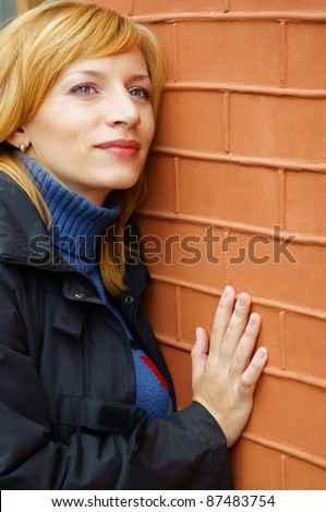 portrait of a young cute woman at wall