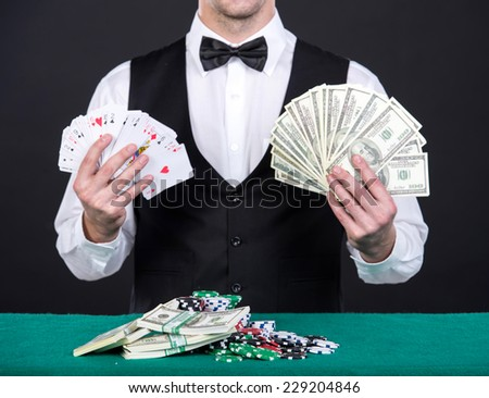 Portrait of a young  dealer with playing cards and money in hands. - stock photo