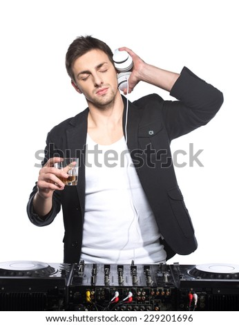 Portrait of a young DJ standing at the mixer on a light background. - stock photo