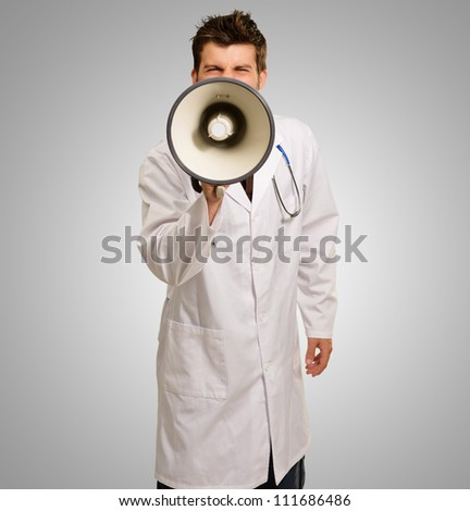 Portrait Of A Young Doctor Holding Megaphone On Gray Background