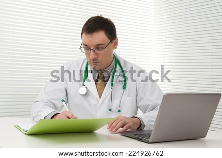 Portrait of a young doctor using his laptop computer - stock photo