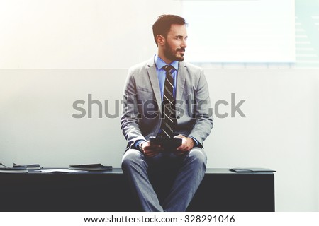 Portrait of a young dreamy male managing director in luxury suit resting after work on his digital tablet, successful man ceo thinking of new ideas while sitting with touch pad in corporation office  - stock photo