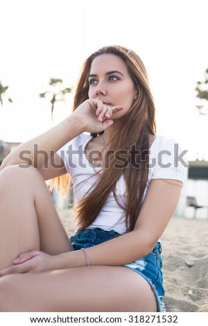 Portrait of a young dreamy woman enjoying tranquility while sitting alone on the beach in summer day, beautiful stylish hipster girl resting after walking along the waterfront during weekend  - stock photo