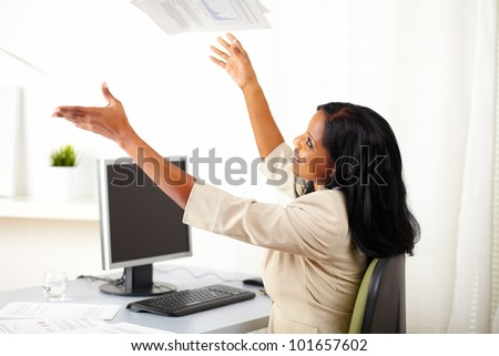 Portrait of a young entrepreneur woman celebrating a business success while looking up - stock photo