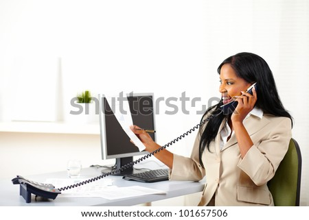 Portrait of a young executive on phone while looking to documents - stock photo
