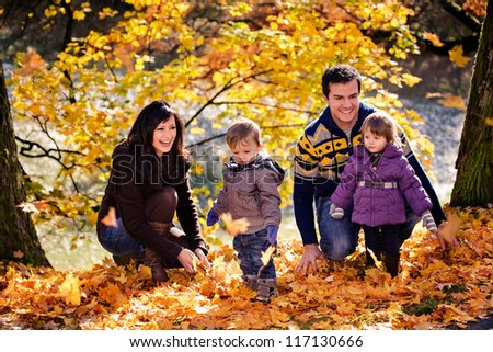 portrait of a young family in the autumn park - stock photo