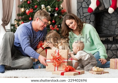 Portrait of a young family with children at home New Year's Eve by the fireplace and near the Christmas tree - stock photo