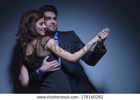 portrait of a young fashion couple dancing while looking away from the camera. on a dark blue background - stock photo