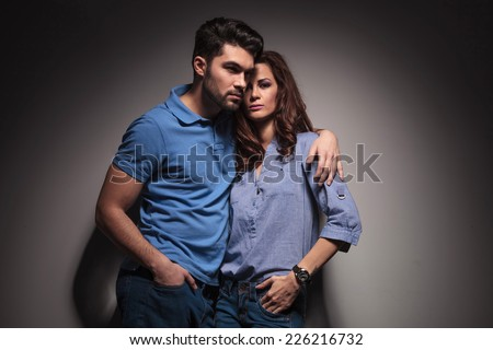 Portrait of a young fashion couple posing with their hands in pockets. - stock photo