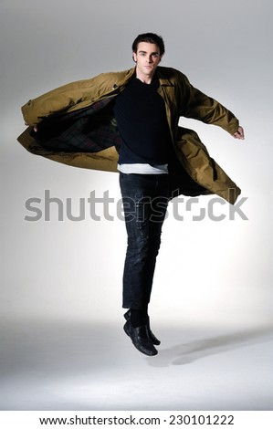 portrait of a young fashion male jumping on light background