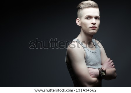 Portrait of a young fashionable man in trendy shirt posing over grey background with hands crossed. Perfect skin and haircut. Hipster style. Studio shot - stock photo