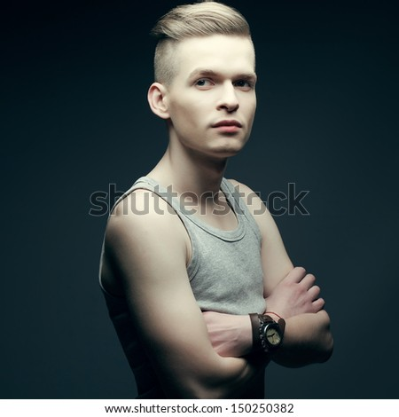 Portrait of a young fashionable man in trendy shirt posing over grey background with hands crossed. Perfect skin and haircut. Vintage dress watch on a hand. Hipster style. Studio shot - stock photo