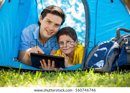 Portrait of a young father and his son using a tablet computer during a camping trip and smiling - stock photo