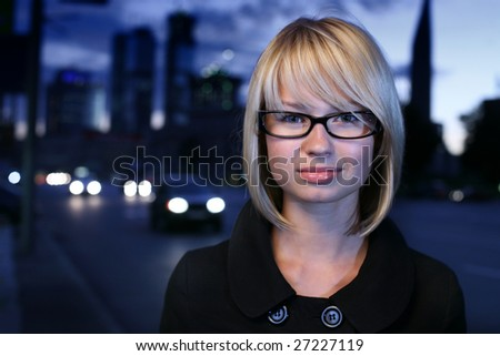 Portrait of a young female businesswoman in night city. Close-up, shallow DOF.