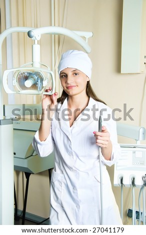 portrait of a young female dentist in the office with equipment