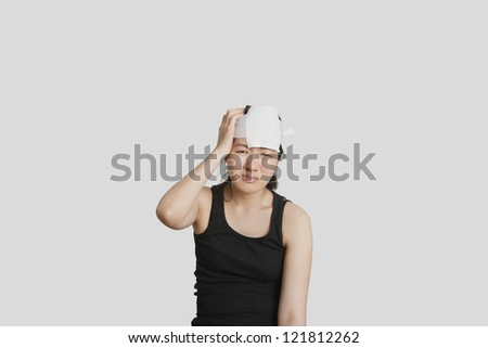 Portrait of a young female in pain with serious head injury - stock photo