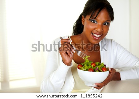 Portrait of a young female looking at you while eating salad at home indoor. With copyspace. - stock photo