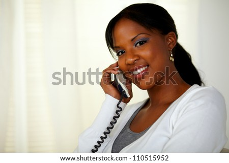 Portrait of a young female smiling at you while talking on phone at soft colors composition