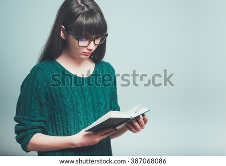 Portrait of a young female student reading a book with glasses isolated on a gray background - stock photo