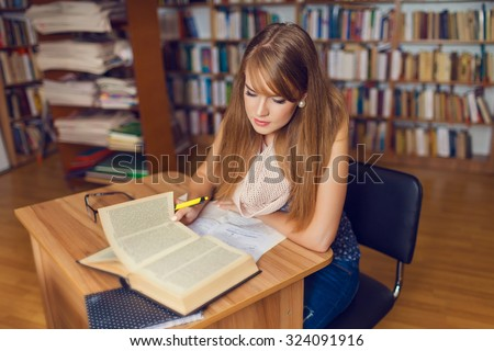 Portrait of a young female student standing in a university library - stock photo