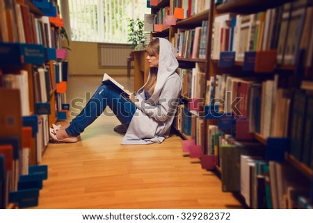 Portrait of a young female student standing in university library - stock photo