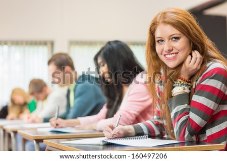 Portrait of a young female student with others writing notes in the classroom - stock photo