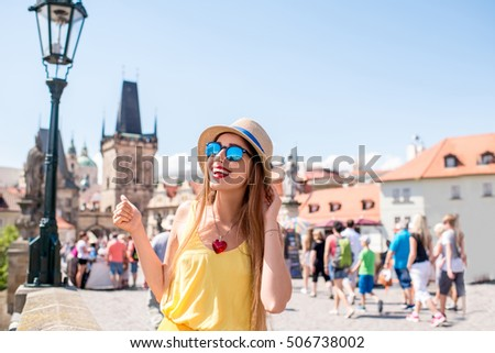 Portrait of a young female tourist on Charles bridge in the old town of Prague.