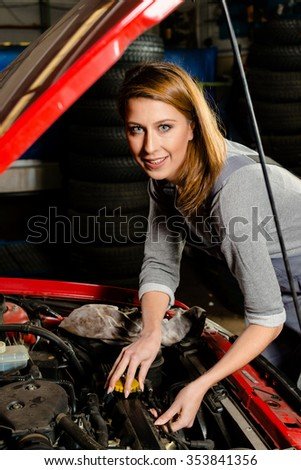 Portrait of a young female trainee auto mechanic fixing the engine of a car with open hood in a garage. Concept for the fact that more and more women participate in jobs previously typical for men.  - stock photo