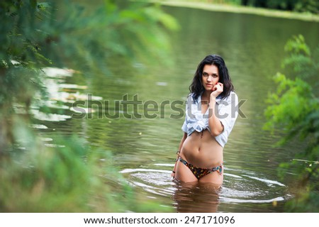 Portrait of a young fit brunette woman wearing white shirt and colorful panties standing in river water in summer - stock photo
