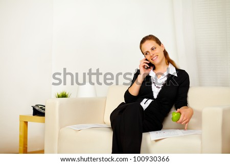 Portrait of a young friendly business woman working with documents while is eating a green apple and speaking on the phone - stock photo