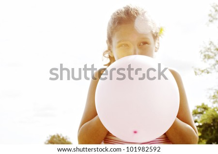Portrait of a young girl blowing up a pink balloon in front of her face. - stock photo